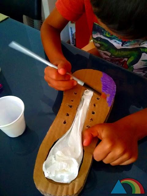 Niño pintando un zapato hecho con cartón