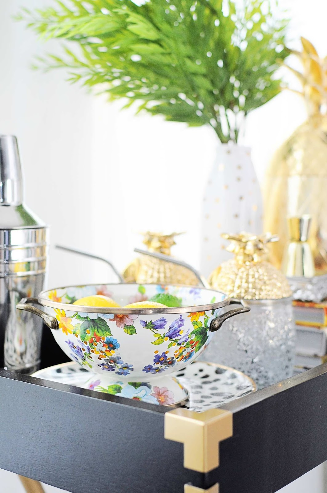 A butler tray is used as a bar in a chic and stylish black, white and gold dining space.