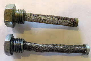 Two drain plugs with mesh strainers, one longer than the other.
