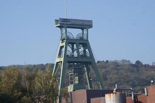 Ein Zechenturm in grün gestricken, mit zwei Seilscheiben. Im Hintergrund ist die Halde zu erkennen.