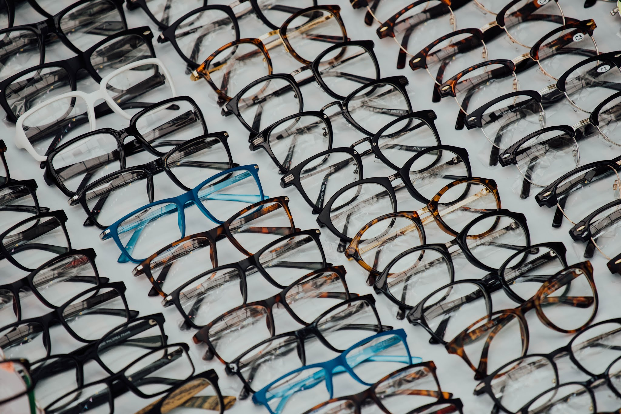 A white background with lots of glasses lined up on it