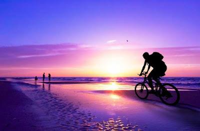 Naik sepeda di pinggir pantai saat matahari terbenam