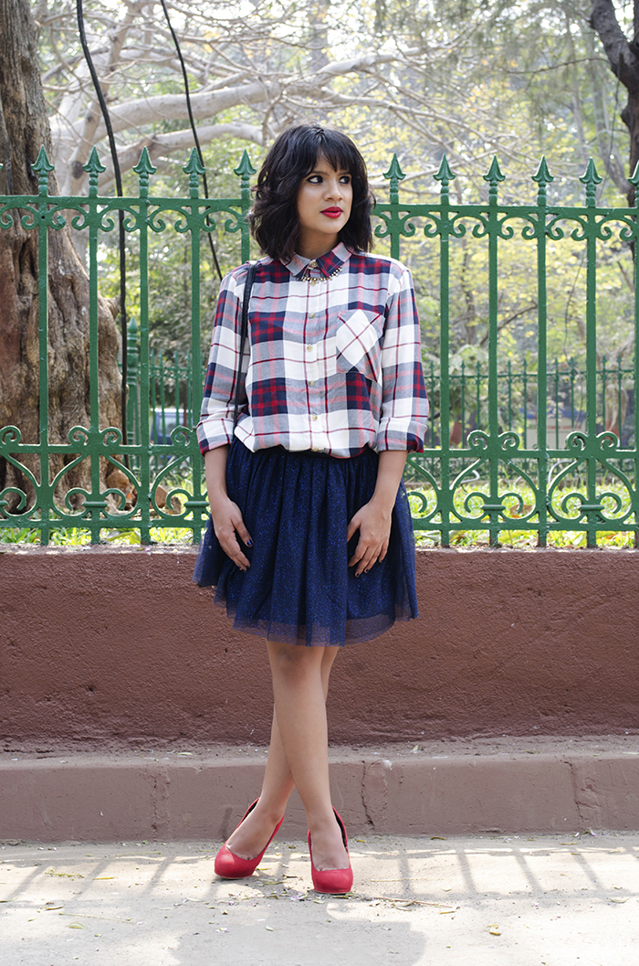 Image of blogger Dayle Pereira wearing a check plaid shirt with a navy blue tulle skirt, red lips, wavy bob and red pumps