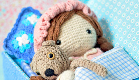 Crochet pattern amigurumi doll girl in bed in pajamas with teddy bear