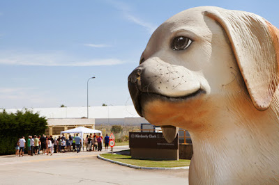 Entrada fábrica Kimberly Clark celebrando 40 aniversario con perro Scottes en primer plano