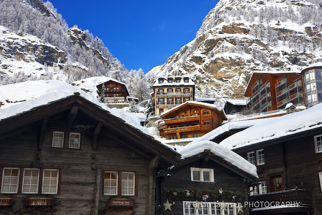 Quaint Alpine village houses climb the slopes of the Swiss Alps.