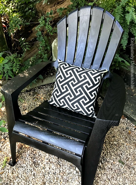 Black Adirondack chair with white and black pillow on gravel patio