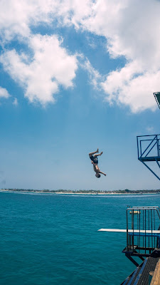Image of a person doing diving tricks off a diving board into the sea.