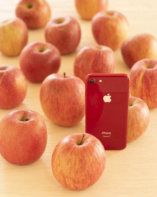 沢山のリンゴにアップルのiPhoneを置く