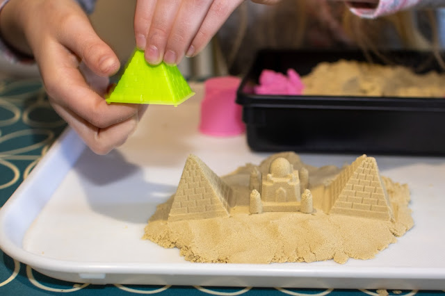 A close up of a plastic pyramid mould being removed from some play sand