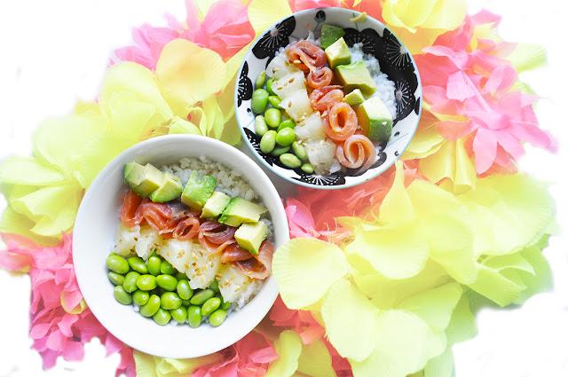dos platos de poke bowls, uno mas grande, llevan arroz, edamame, piña, aguacate y salmón. los platos estan rodeados de collares hawaianos de flores falsas amarillas y rosas