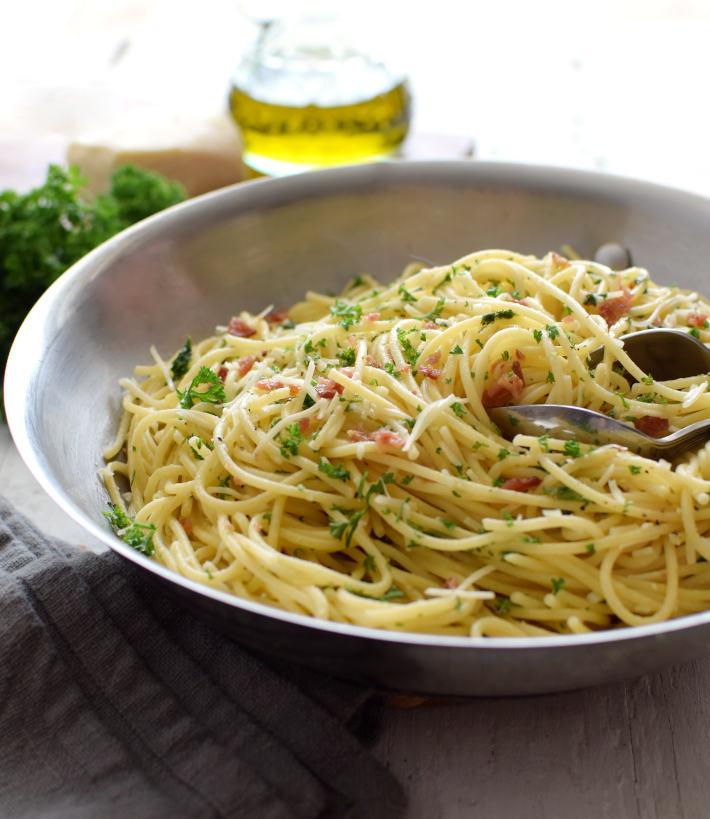 Espaguetis con ajo y perejil al contraluz, para apreciar las texturas y colores de los ingredientes