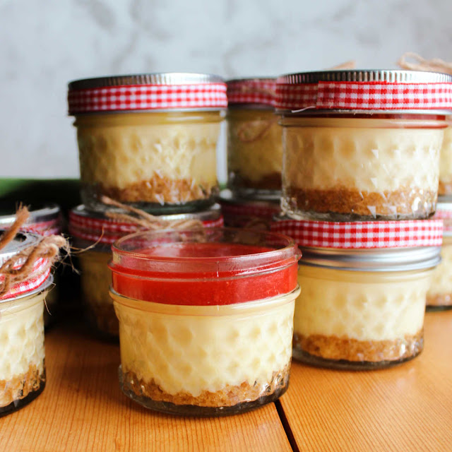 mini baked cheesecakes in jars with strawberry topping and red gingham ribbons