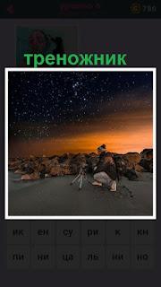 мужчина ночью с треножником смотрит на звездное небо