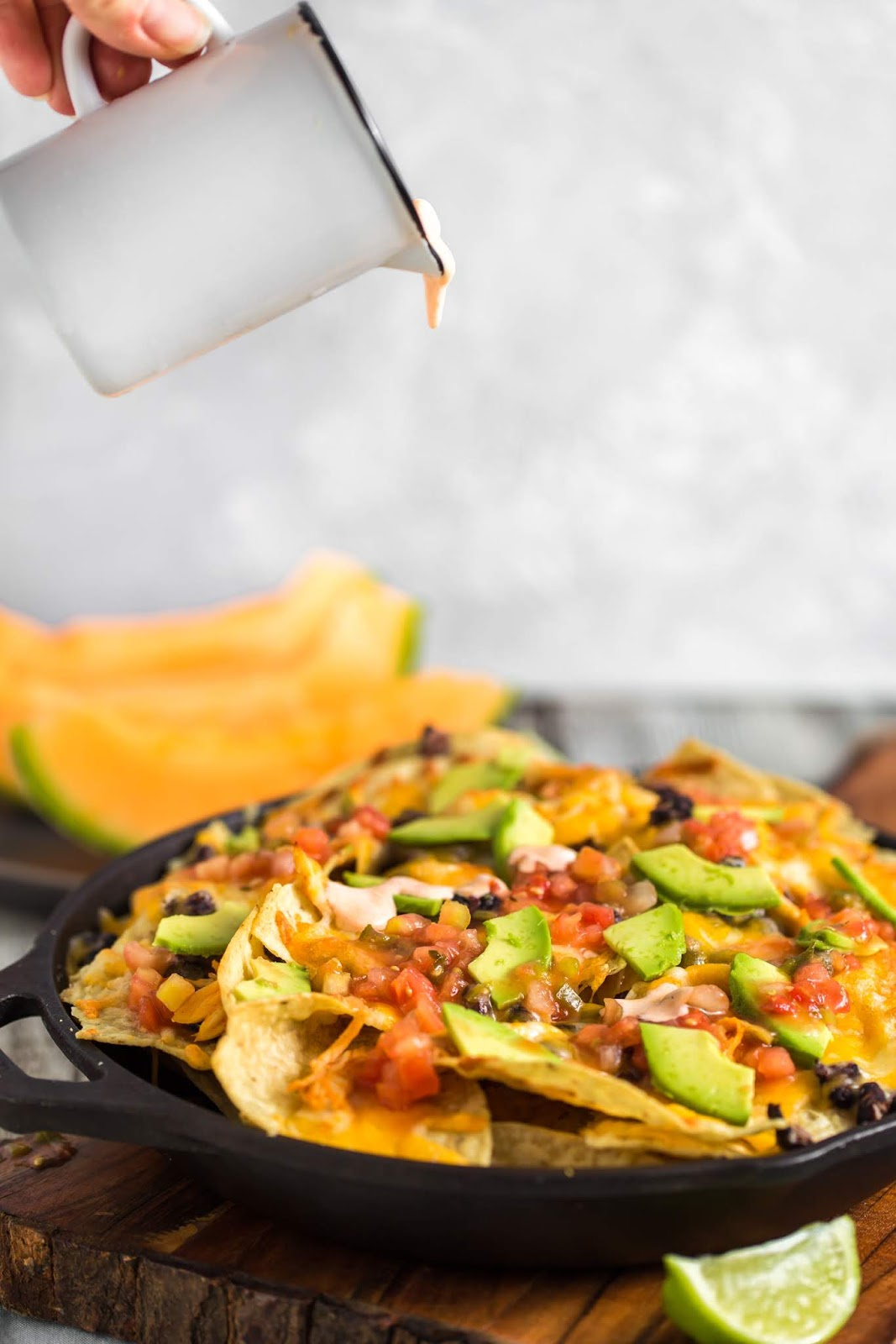 Hand pouring cup of sauce onto plate of nachos
