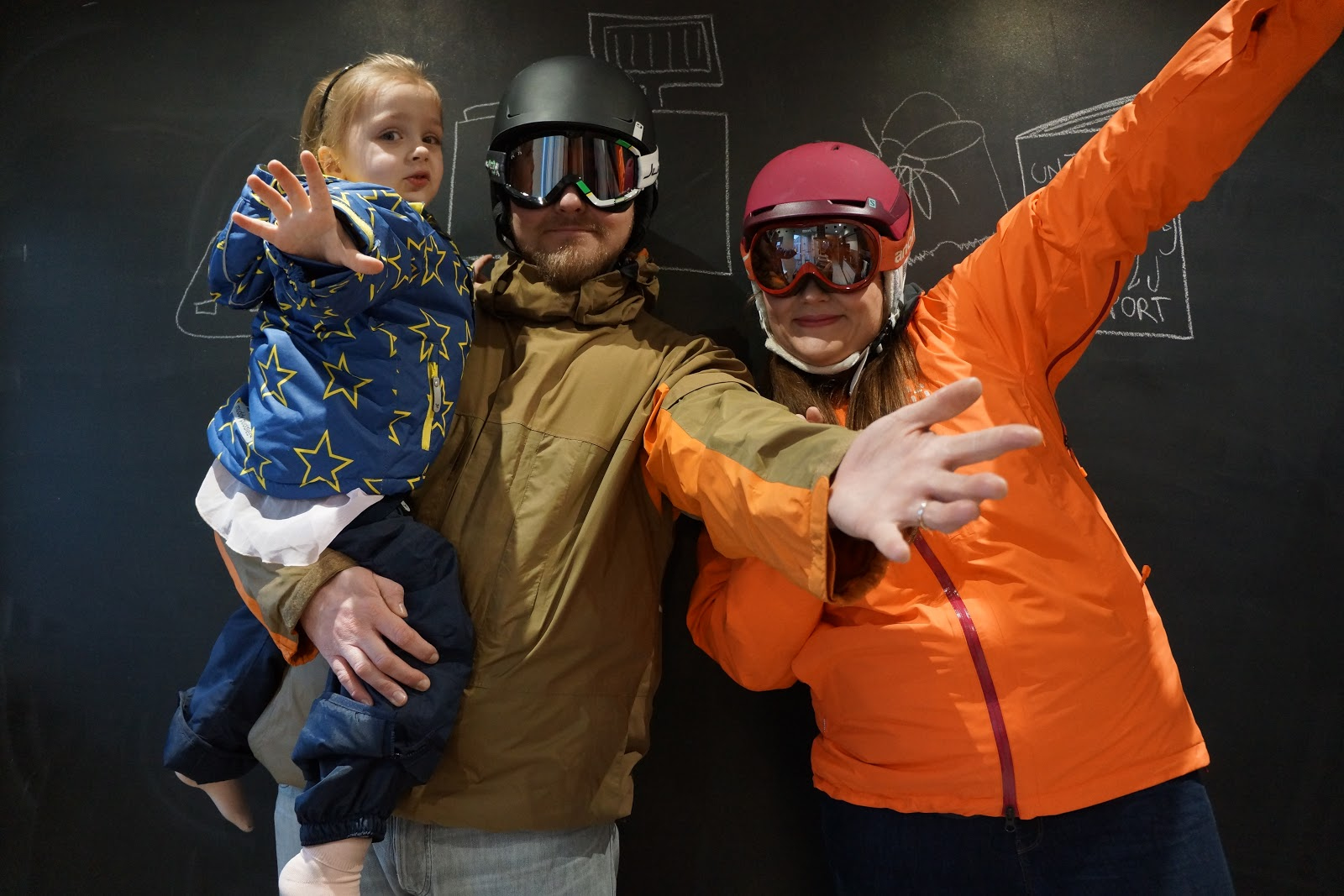 family of three wearing ski gear