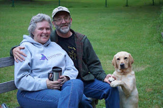 A woman and a man sit on a bench outside. The man has his arm around the woman. A yellow Labrador retriever sits and rests her front paws on the man's knee.