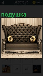 Красивый кожаный диван с подушками по бокам стоит одиноко около стены на ножках