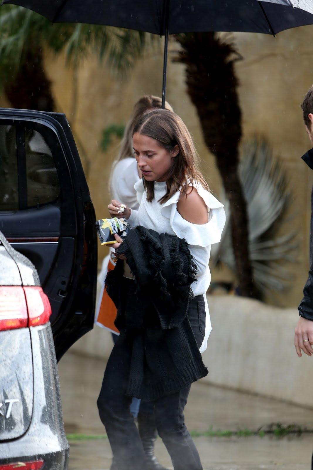 Alicia Vikander leaves her car in heavy rain In Venice Beach