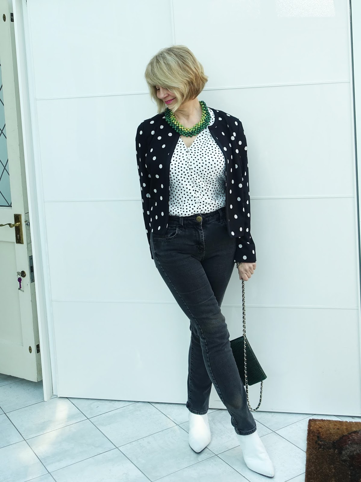 Polka dot jacket and top worn with black jeans and white boots with green accessories