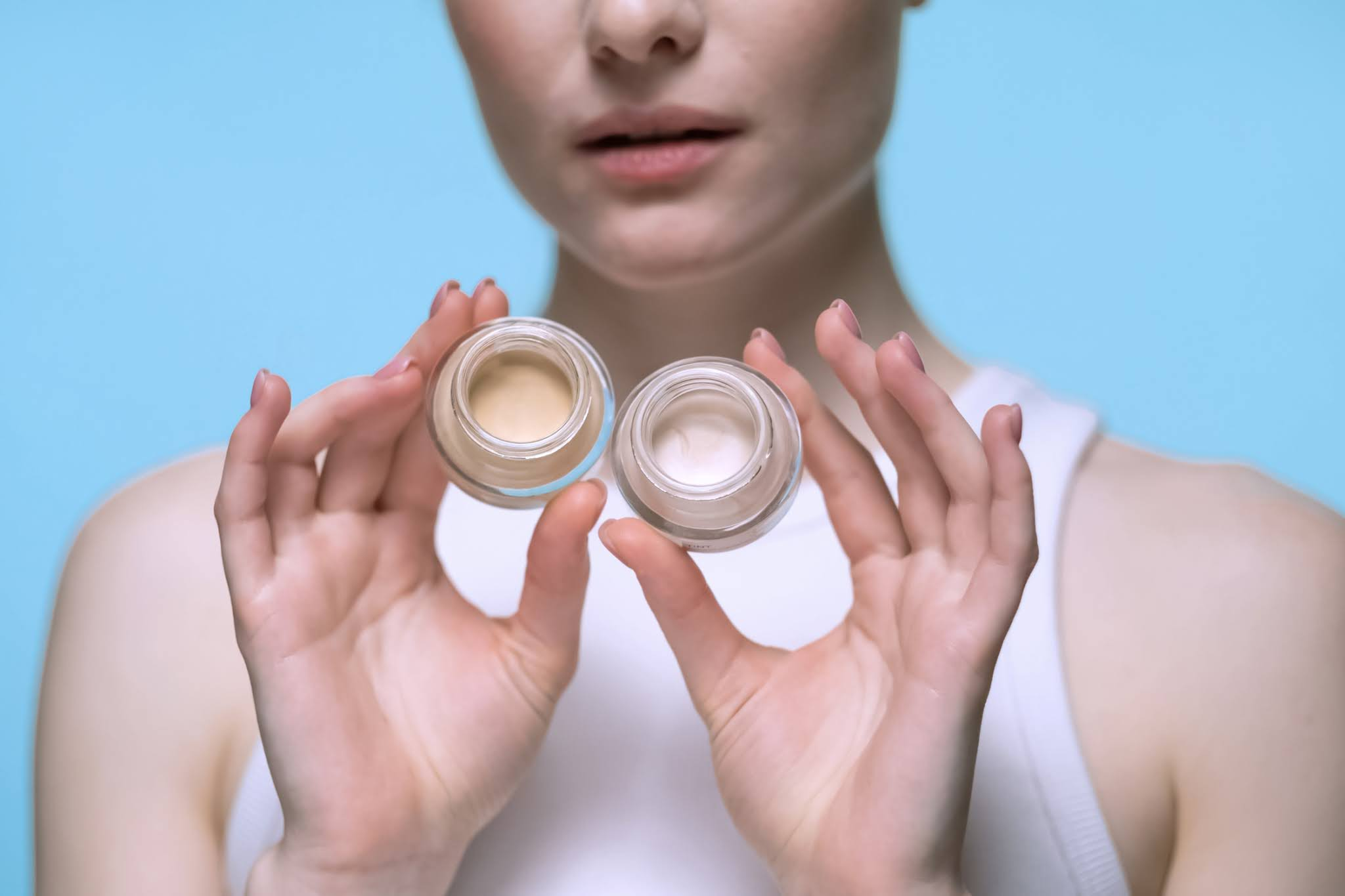 woman is holding two makeup products in her hands and showing them to the camera