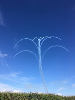 photo of vapour trials from the red arrows display team, against a blue sky