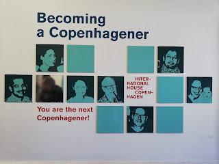 """Sisääntuloaulan seinällä oli kuva, missä on kuvia kööpenhaminalaisista. Mukana on peili ja vieressä teksti: """"Sinustakko seuraava kööpenhaminalainen?"""""""