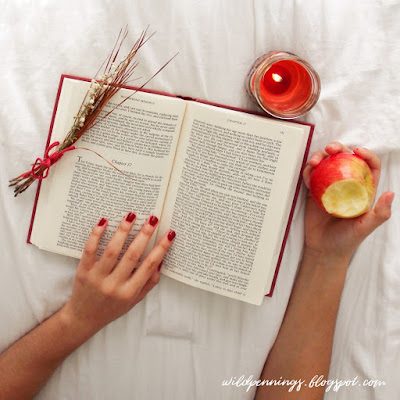 hands on book next to candleand apple against white background