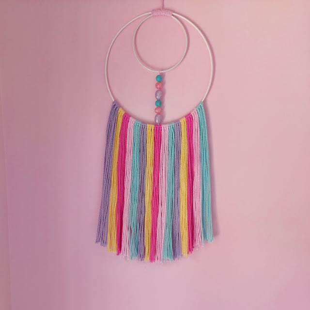 Colourful yarn hoop wall hanging for a baby's nursery
