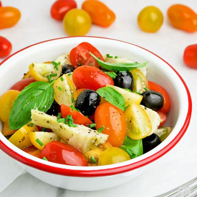 Zomersalade van cherrytomaatjes, artisjokkenharten, olijven en basilicum