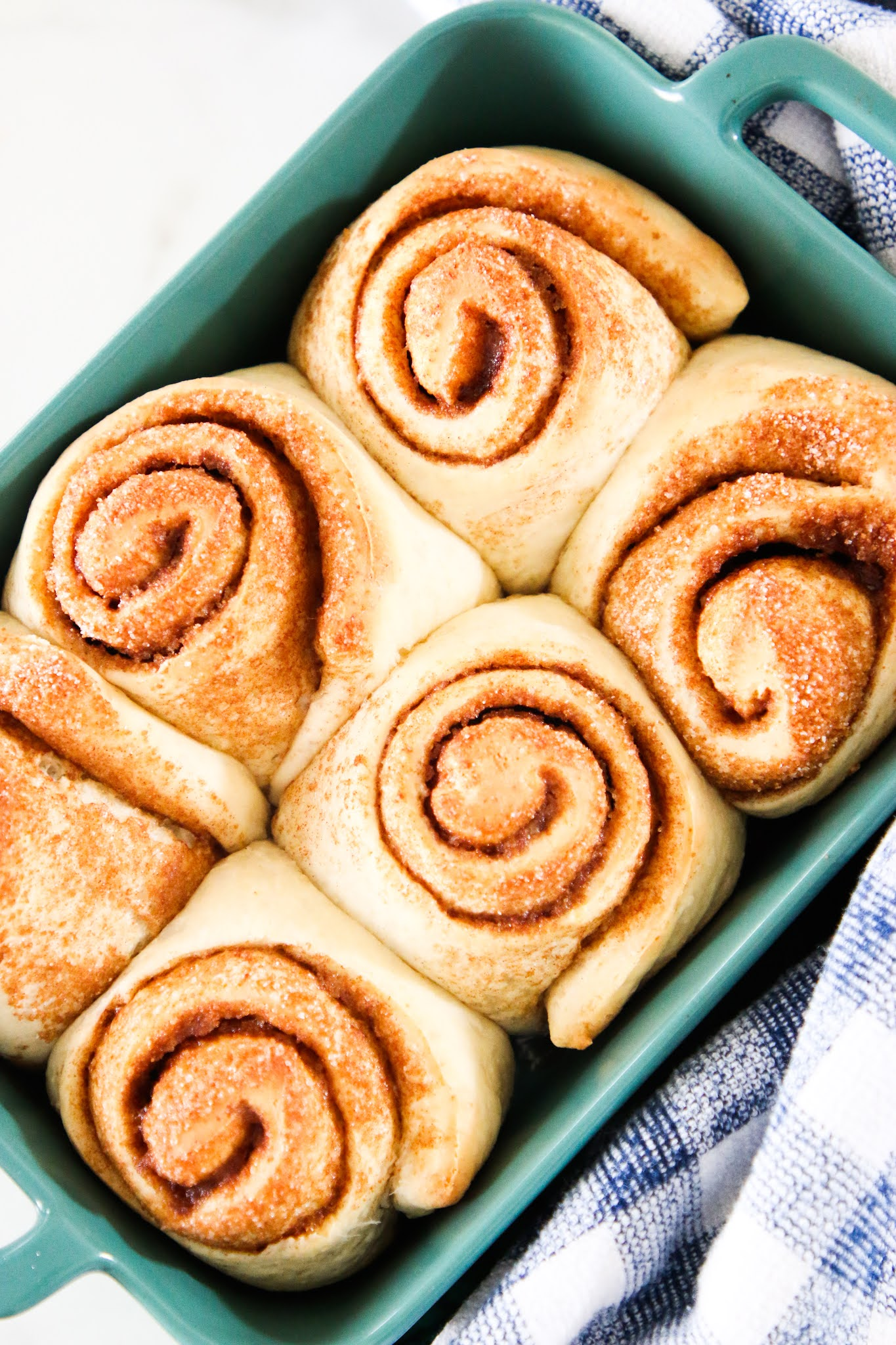 Six cinnamon rolls in a green baking dish with a blue dish towel in the background.