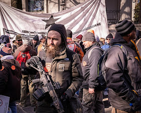 Group of people standing outside; man in front holding a semi-automatic rifle.