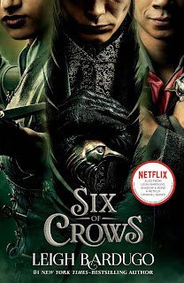 Book cover for the Six of Crows Netflix tie-in edition, featuring Inej, Kaz, and Jesper in a dark green theme