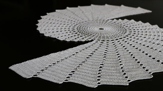 Almost a full view of an off-white Fractal doily on a dark background.