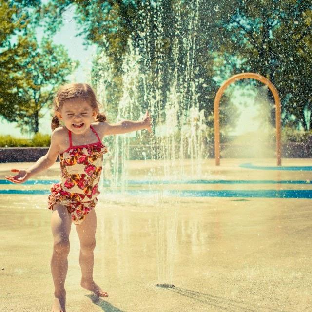 Hija jugando en parque de agua