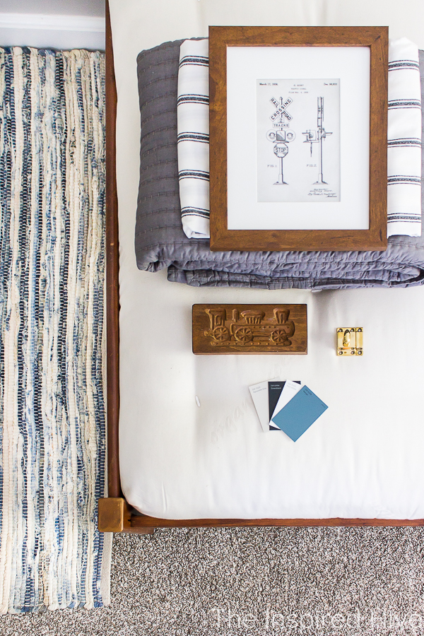 Flatlay photo of bedding, vintage train art, hardware, and paint swatches on a mattress from The Futon Shop