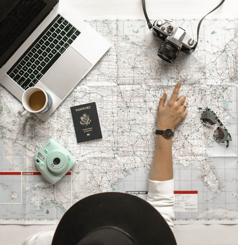 person pointing at map with coffee, laptop, polaroid, passport, camera