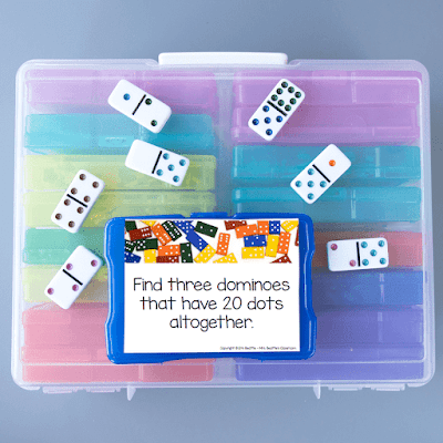 Photo of task card and dominoes on top of large container of task card bins.