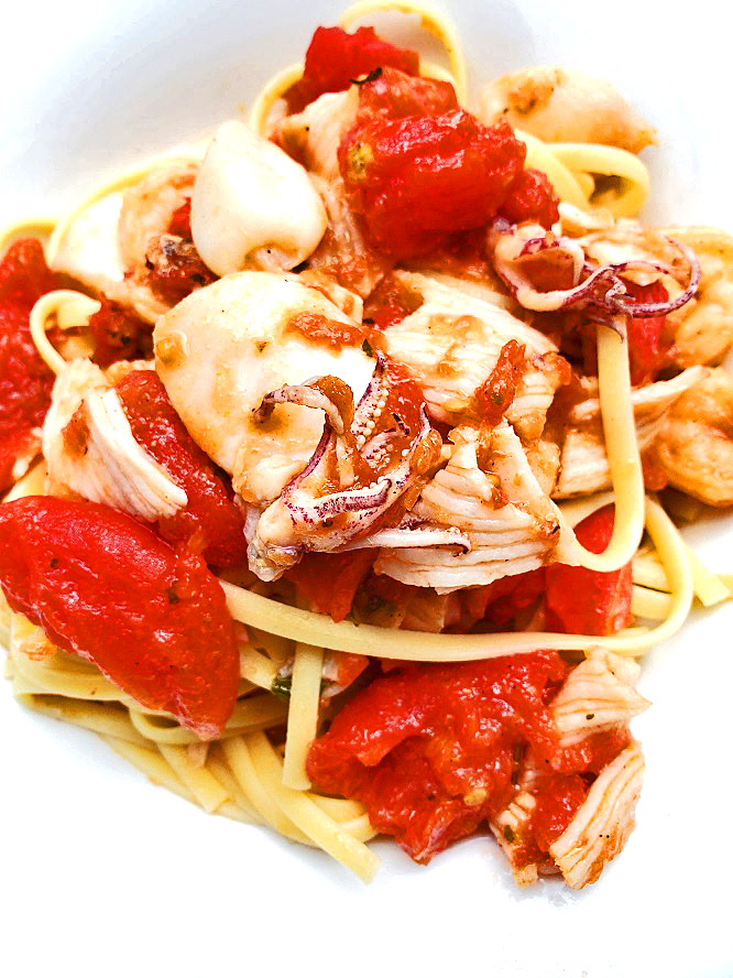 this is a dish of vermicelli pasta with a fish stew on top that includes shellfish and regular white fish along with a rich wine tomato based sauce and called Cioppino  a dish based out of San Francisco