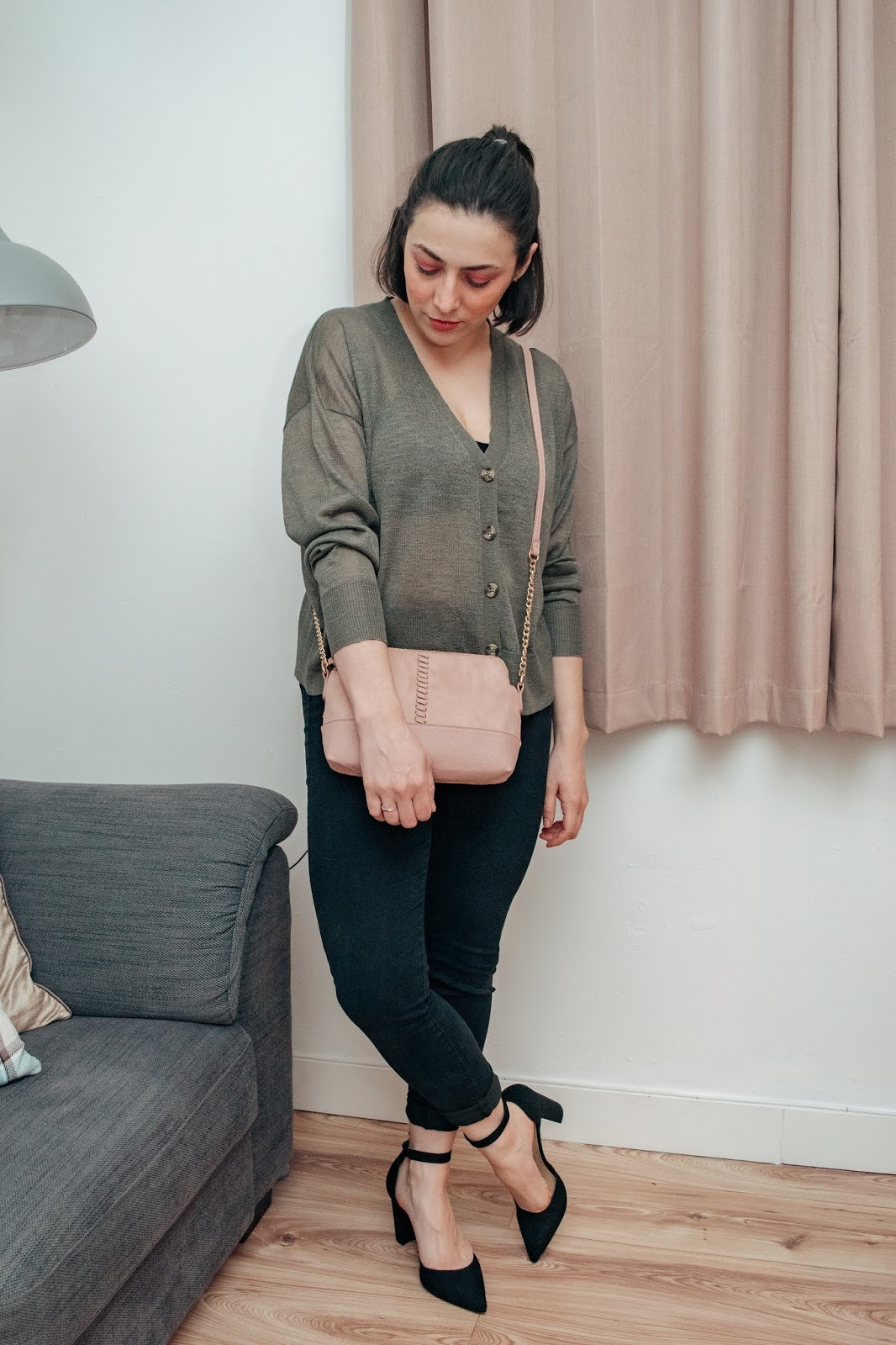 Standing styling a khaki green boxy cardigan with black jeans, black heels and a pink cross body bag.