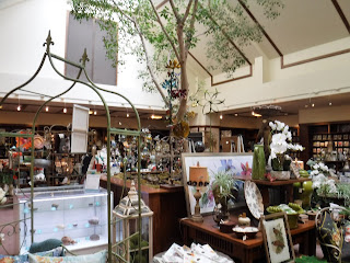 souvenirs of all kinds, most embellished with floral patterns, adorn a well lit gift shop at Lauritzen Gardens