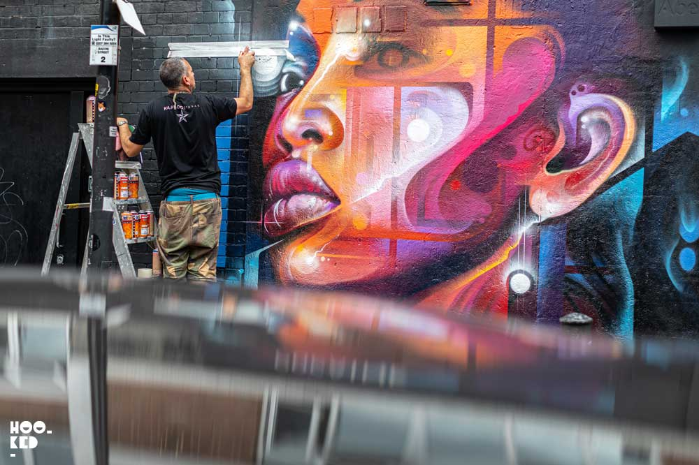 Brick Lane Street Art - Artist Mr Cenz at work on a mural on Bacon Street, London