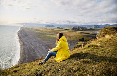 Young woman traveling alone enjoying view of Vik beach
