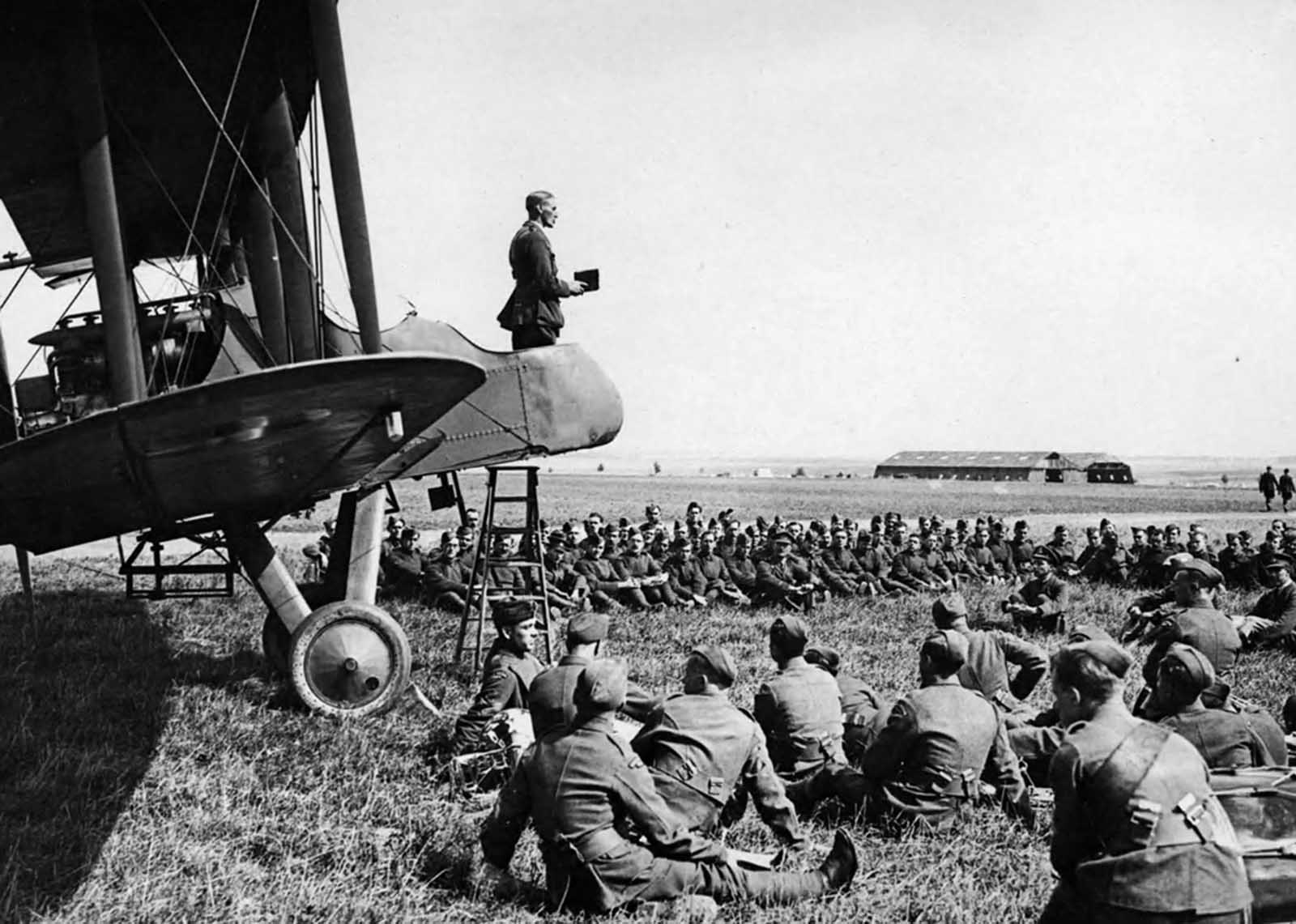 A Sunday morning service in an aerodrome in France. The Chaplain conducting the service from an aeroplane.
