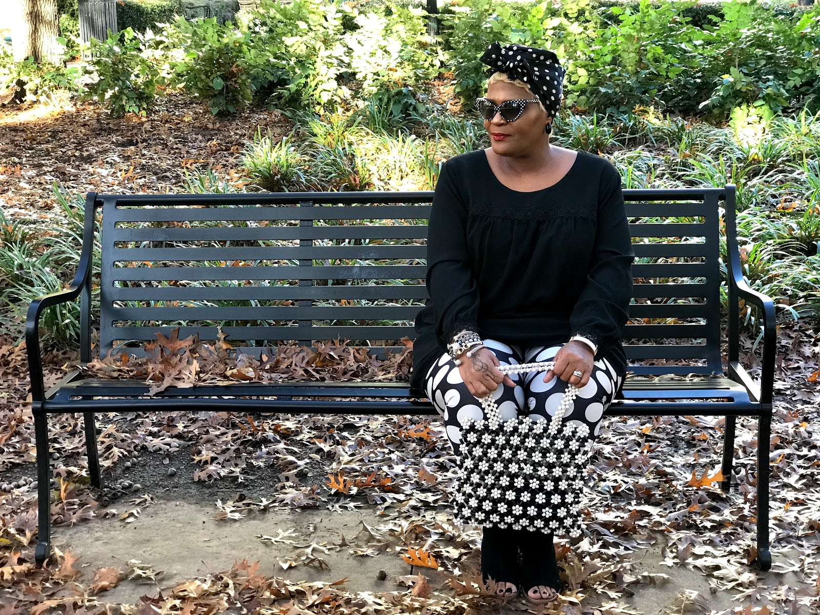 Sitting on a bench sharing outfit ideas, shoes, polka dot leggings, handbag, polka dot shades