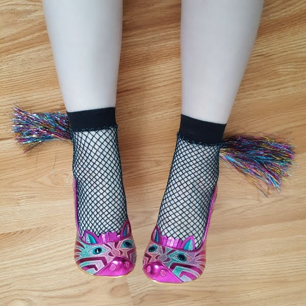 feet wearing metallic zebra shoes with faces on front and multi coloured tinsel tail at heel