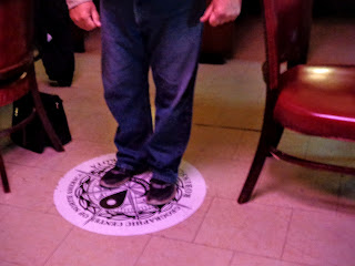 stand on the sticker designating the geographic center of North America at Hanson's Bar in Robinson, North Dakota