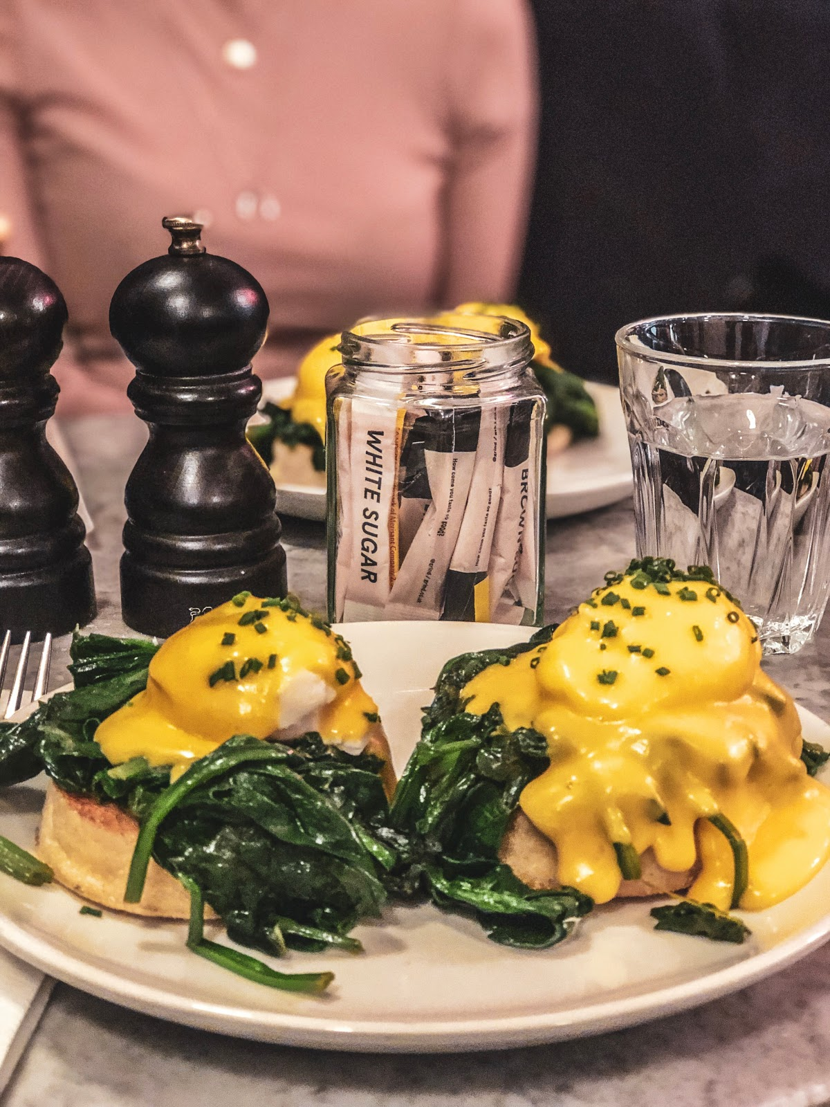 A plate of poached eggs in hollandaise sauce with a side of spinach