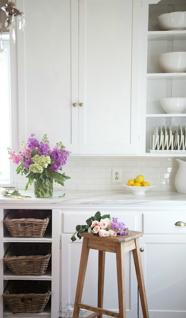 Marble counters in kitchen with flowers and stool