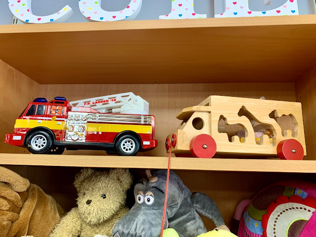 Shelves in a charity shop showing a fire engine and a wooden shape sorter toy for sale